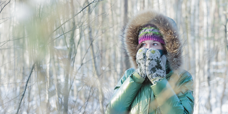 Young woman in winter frost forest hiding her face in woolly scarf and mittens outdoors